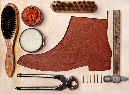 Silhoutte of leather chelsea boots in the center with shoe maintenance set and reapir set.Top view.Wooden background.Concept reapir and care shop