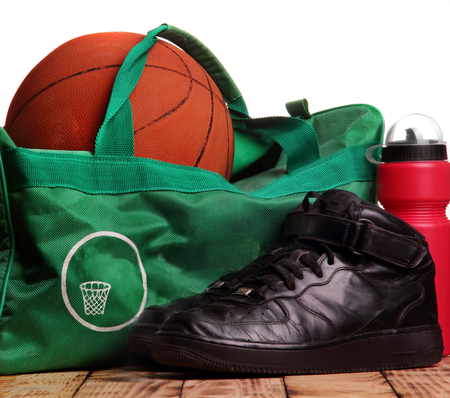 High black sneakers , Sport bag for basketball, Basketball ball inside the bag, sport bottle with water near.Top of photo white background down wooden background.Background.Concept basketball training