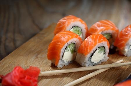 Philadelphia roll sushi with salmon, prawn, avocado, cream cheese. Sushi menu. Japanese food Closeup.Wooden background
