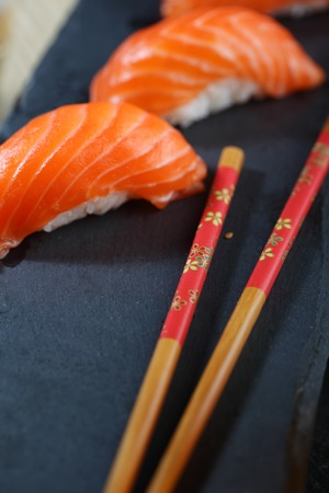 Sashimi sushi set with Philadelphia roll sushi on black slate plate background.Nigiri.Closeup.Selective focus