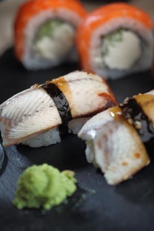 Sashimi sushi set with Philadelphia roll sushi on black slate plate background.Nigiri.Closeup