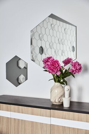 Vase with beautiful blooming peonies on wooden commode against white wall with hexagonal mirror .Background.