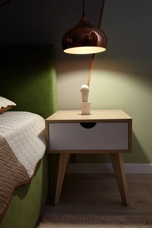 Bedroom lamp on a night table near sleeping bed.Dark room.