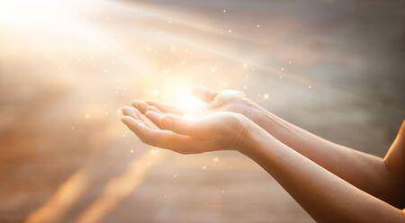 Mains de femme priant pour la bénédiction de Dieu sur fond de coucher de soleil