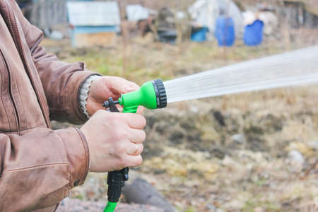 Man turns on the hose for watering plants with a sprayer. include a spray bottle for watering plants.