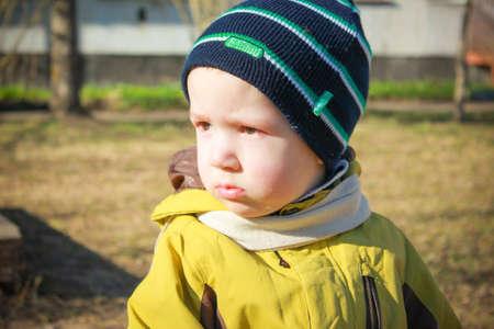 Resentful, sad little boy sitting in the garden on the Playground. Portrait of a sad, hurt child.