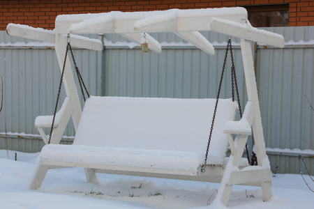 Snow-covered garden swing. wooden garden swing on chains, all in the snow. swing in winter.