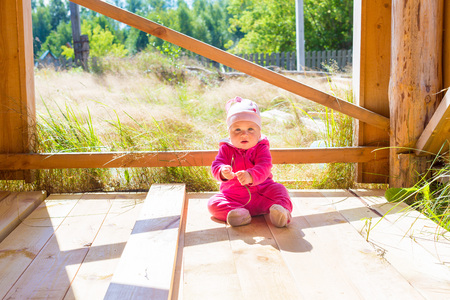 romper: baby summer Romper in pink on the wooden deck