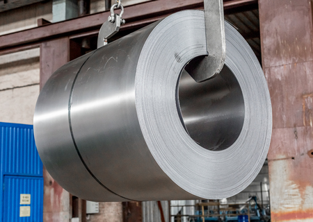 roll of sheet steel, transported by crane at the factory