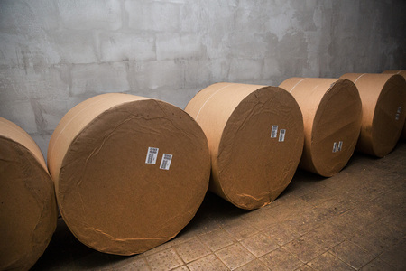 large rolls of paper for printing lie against the wall Фото со стока