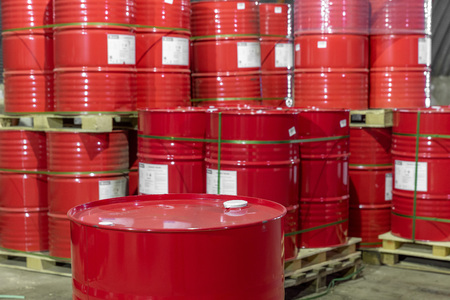 a stack of red barrels on pallets in a warehouse