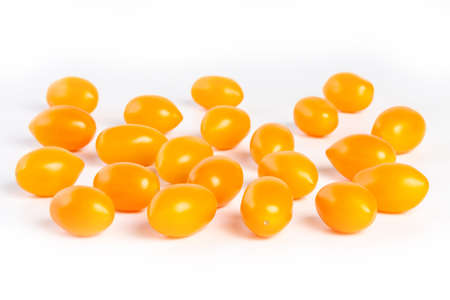 multiple yellow cherry tomatoes on a white background with shadow