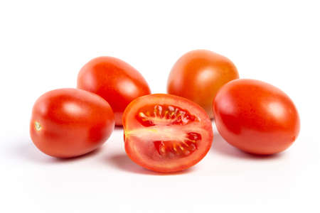 a group of tomatoes on a white background, with shadows. One tomato cut, studio photo, isolate, tomatoes washed