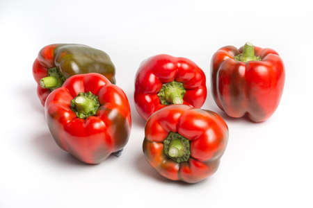 a group of Bulgarian sweet peppers on a white background, with shadows. studio photo, isolate, peppers washed. Peppers are red, with green spots