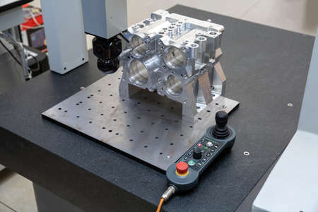 The coordinate measuring machine measures the aluminum part turned by the cnc machine Stock Photo