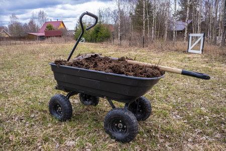 humus in a four-wheeled garden cart. Cloudy spring day