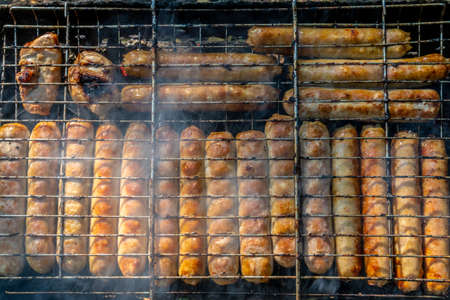 sausages are baked on coals in a metal grill. Sunny evening