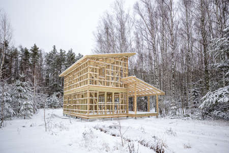 frame house construction in winter, under the snow, in the forest. Fresh wood, frame of a two-story house Stock Photo