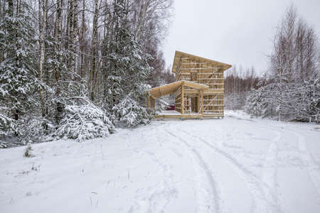 a frame house under construction in the forest. Dense forest, winter Stock Photo