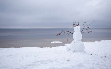 a snowman on the shore of a calm sea on a cloudy winter day.