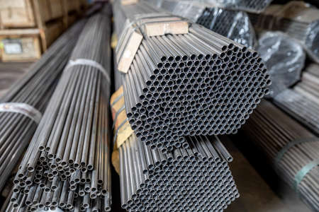 warehouse of thin steel pipes in the metalworking industry. Stock Photo