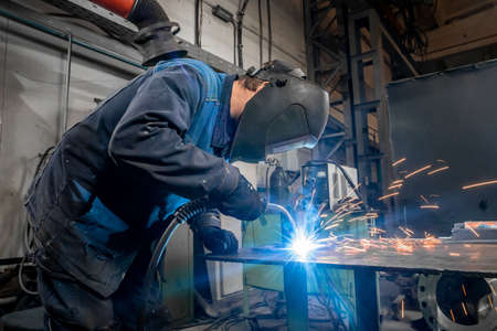 welding work at a metalworking plant. A helmeted welder welds a metal part on a welding table