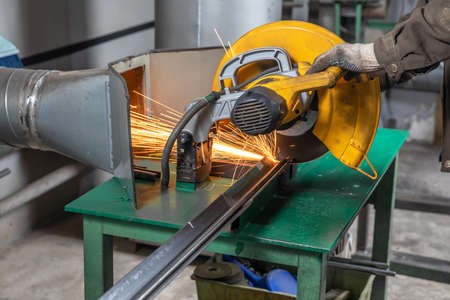A worker cuts off a steel pipe on special equipment with a hood