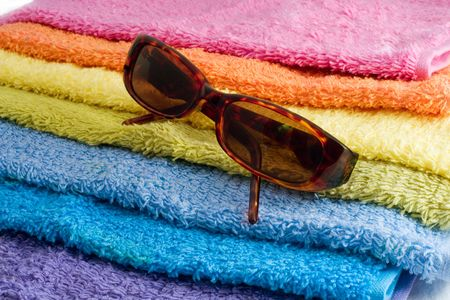 sunglassess: sunglassess on a pile of multicolor towels