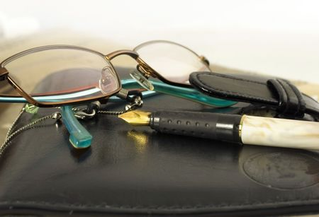 eyeglasses and paen on a black leather day planner