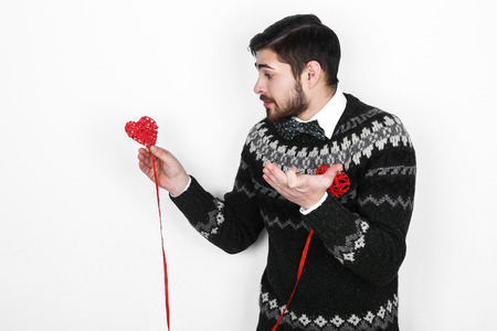 a situation alone: Young handsome bearded man in a knitted sweater with a decor in the form of hearts shows the situation alone on Valentines Day Stock Photo