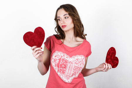 temptress: Young beautiful girl with long dark wavy hair in a pink shirt holding  red heart near her body, the symbol of Valentines Day Stock Photo