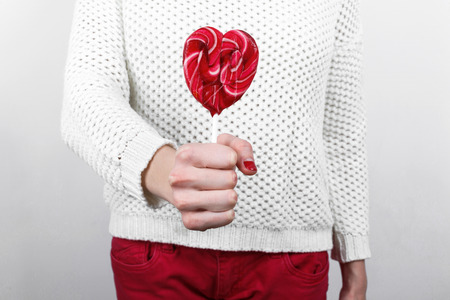 tempt: Girl in white sweater holding in hands sweet tasty lollipop in the shape of heart, St. Valentines Day Stock Photo
