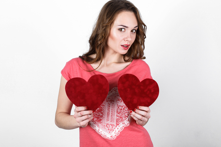 mouth cloth: Young beautiful girl with long dark wavy hair in a pink shirt holding  red heart near her body, the symbol of Valentines Day Stock Photo