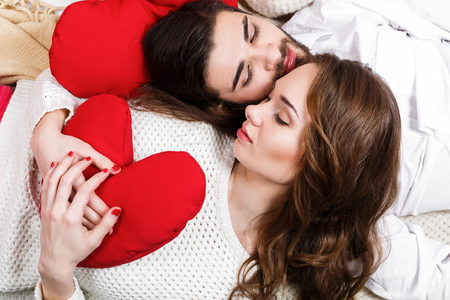 red pillows: Young beautiful stylish couple among red pillows celebrate Valentines Day in a romantic setting