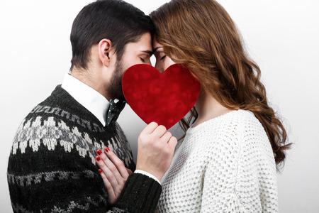 pareja apasionada: Estilo hermosa joven pareja besándose en el amor con el corazón rojo en la mano, que celebra el día de San Valentín