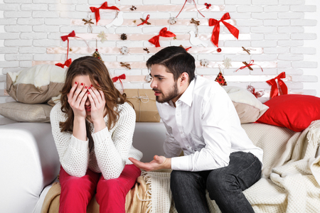 displeasure: Young beautiful couple of loving man and woman sitting in the bedroom at home with displeasure, being at loggerheads. Find out the relationship, divorce, breakup