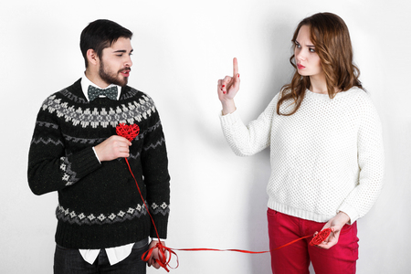 pullovers: Beautiful young love couple in warm knitted pullovers celebrating Valentines Day, performing funny emotional scenes with festive decorations in the form of hearts