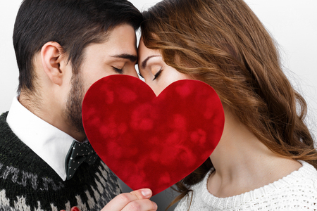 young love: Stylish beautiful kissing young couple in love with red heart in hand, celebrating Valentines Day Stock Photo