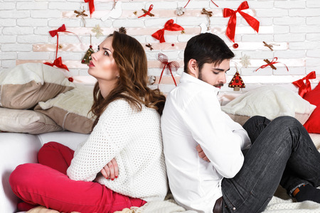 relationship breakup: Young beautiful couple of loving man and woman sitting in the bedroom at home with displeasure, being at loggerheads. Find out the relationship, divorce, breakup