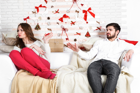 find out: Young beautiful couple of loving man and woman sitting in the bedroom at home with displeasure, being at loggerheads. Find out the relationship, divorce, breakup