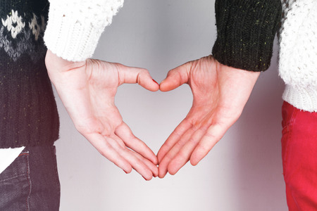 Stylish beautiful young couple in love with heart shaped hands, celebrating Valentines Day