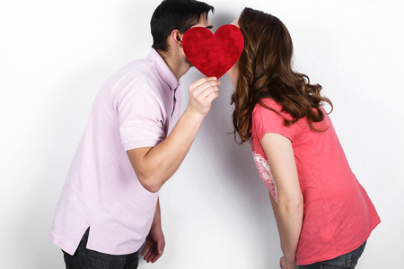 impassioned: Stylish beautiful kissing young couple in love with red heart in hand, celebrating Valentines Day Stock Photo