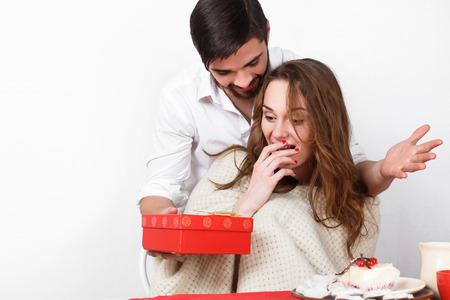 desayuno romantico: Hombre joven que da el regalo a su novia en el d�a de San Valent�n