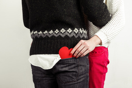 young love: Stylish beautiful young couple in love with red heart in hand, celebrating Valentines Day