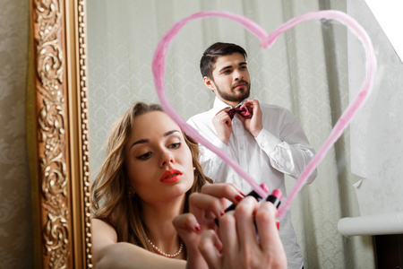 affectionate: Stylish young couple in love in the room going  to celebrate Valentines Day. She confesses his love to his beloved with lipstick on the mirror