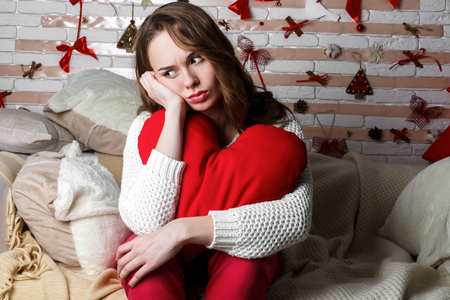 beautiful sad: Young beautiful sad brunette girl in a white knitted sweater with red heart shaped decor sitting alone in bedroom on Valentines Day Stock Photo