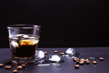 Tasty ice coffee with coffee beans on the table