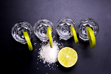 yellow to drink: Glasses of silver and gold tequila with lime in a bar
