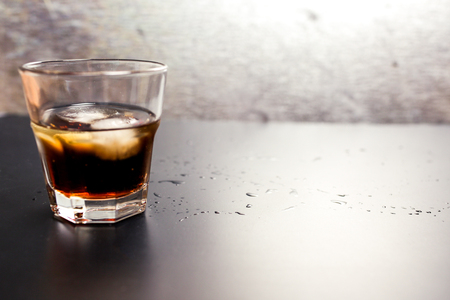 Transparent faceted glass of whiskey-cola alcoholic drink with ice cubes on the table in bar or nightclub