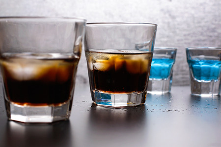 Whiskey-cola with ice and blue liqueur in the bar or restaurant on the table, the bartender profession